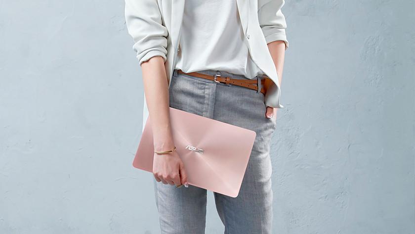 Vrouw houdt 14 inch laptop vast met andere hand in haar zij.