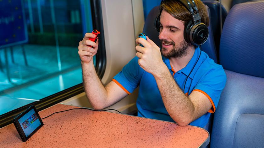 Gamen op de Nintendo Switch in de trein met headset op.