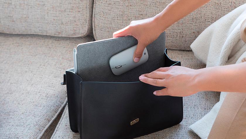Vrouw stopt een 10 inch laptop in een handtas met een muis erbij.