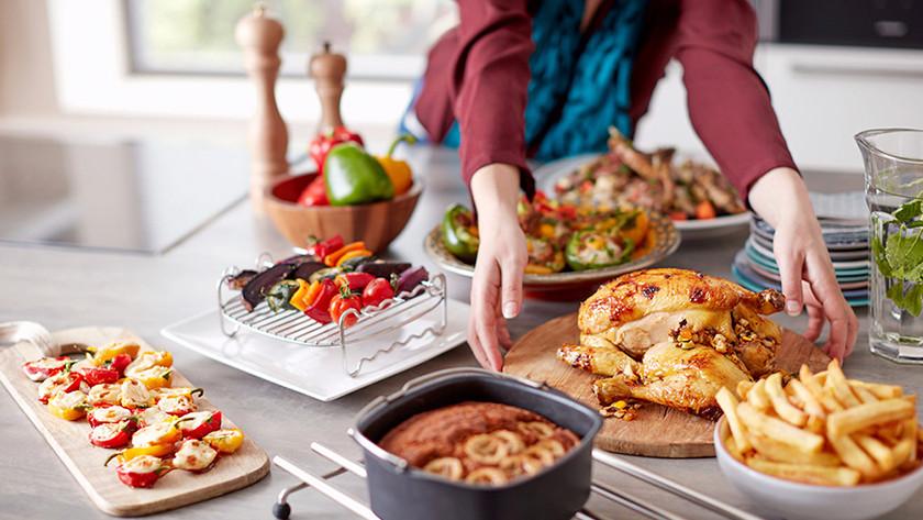 Kip, friet, taart en gegrilde groenten op aanrecht