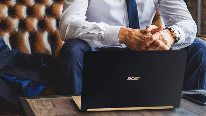 Man works on Acer Swift 7, which is on a table.