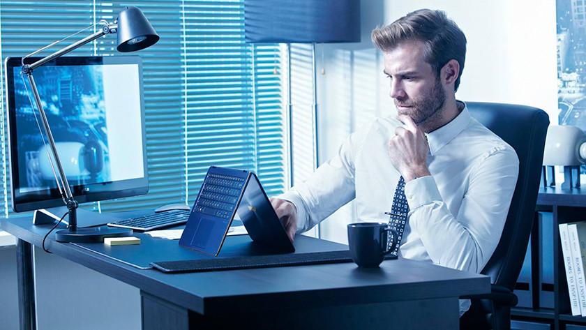 Man achter bureau gebruikt het touchscreen van de Asus ZenBook in tentstand.