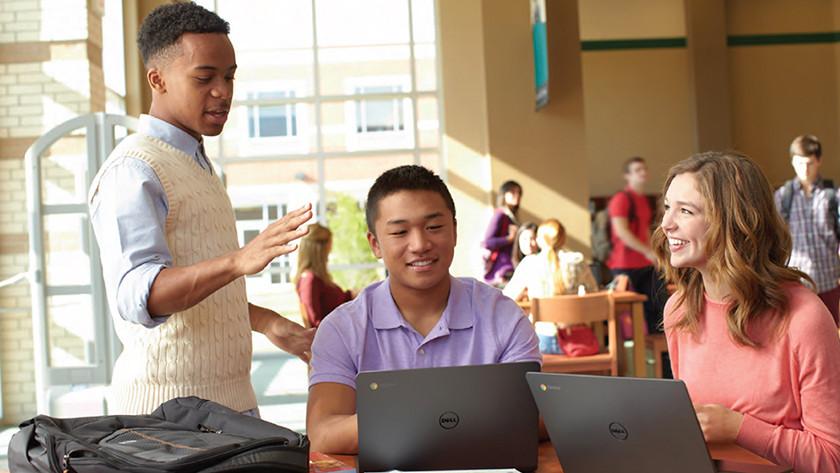 Man praat terwijl 2 anderen op een Chromebook werken.