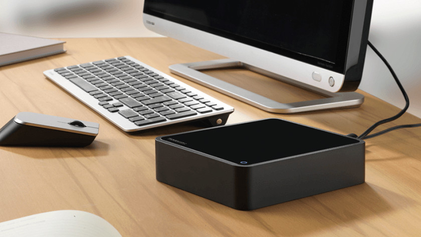 Externe schijf die aan een computer is gekoppeld op een bureau.