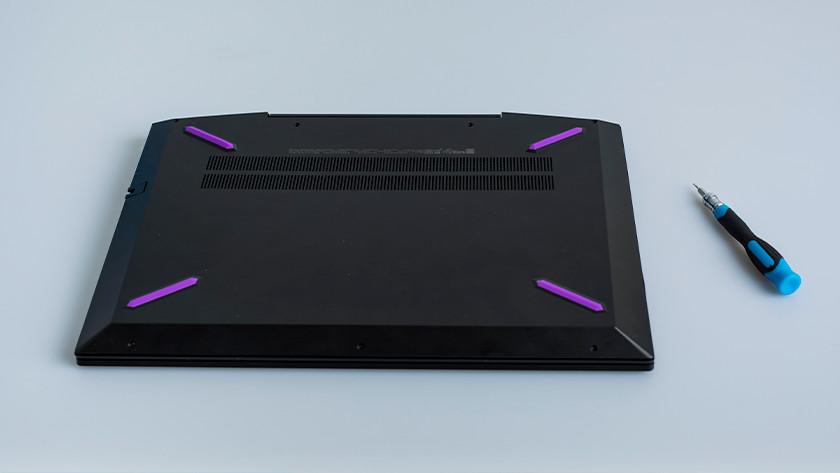 Een schroevendraaier naast de onderkant van een laptop.