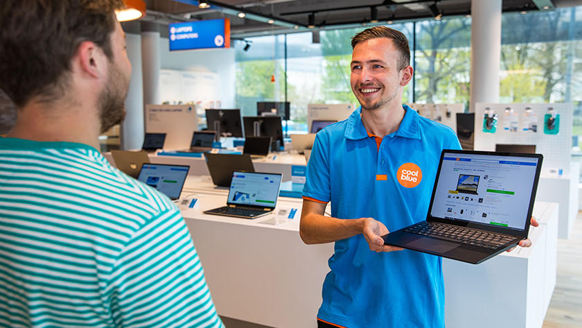 Coolblue employee showing laptop to customer in store.
