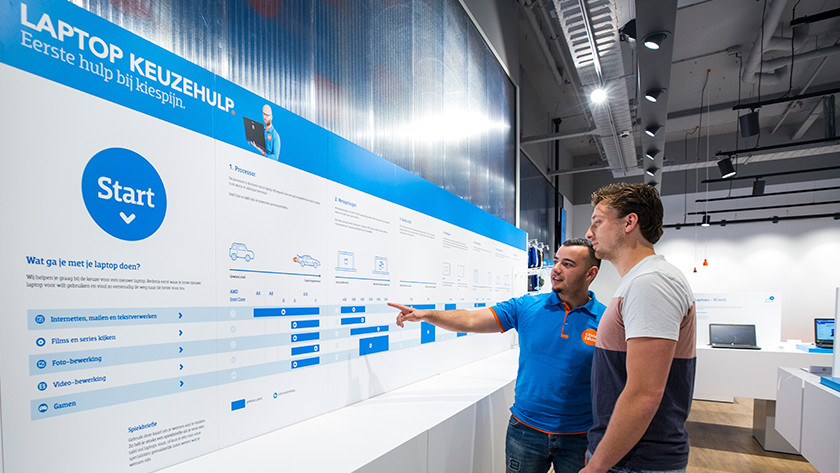 Coolblue medewerker in winkel helpt klant met het kiezen van een laptop.
