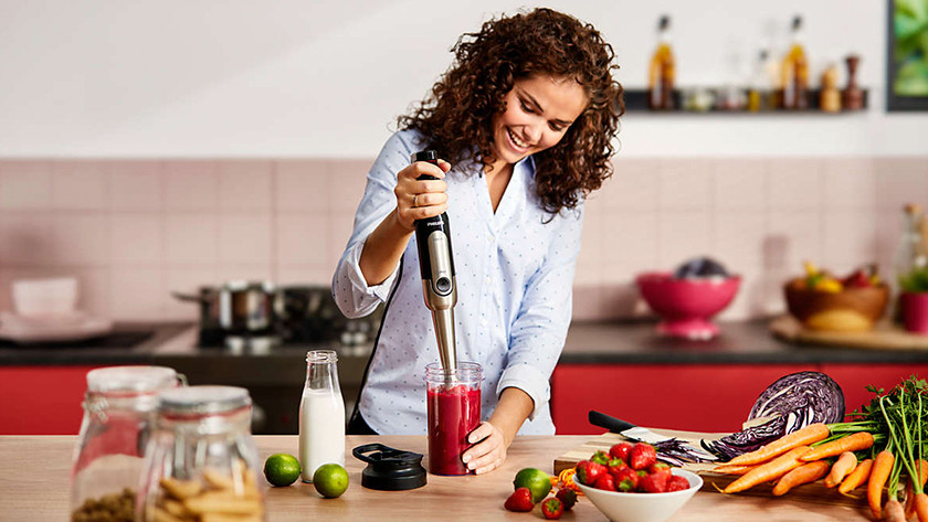 Woman mixes smoothie with immersion blender
