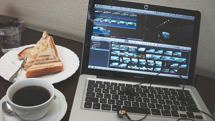 Video's bewerken op een MacBook Pro met een tosti en een kopje koffie.