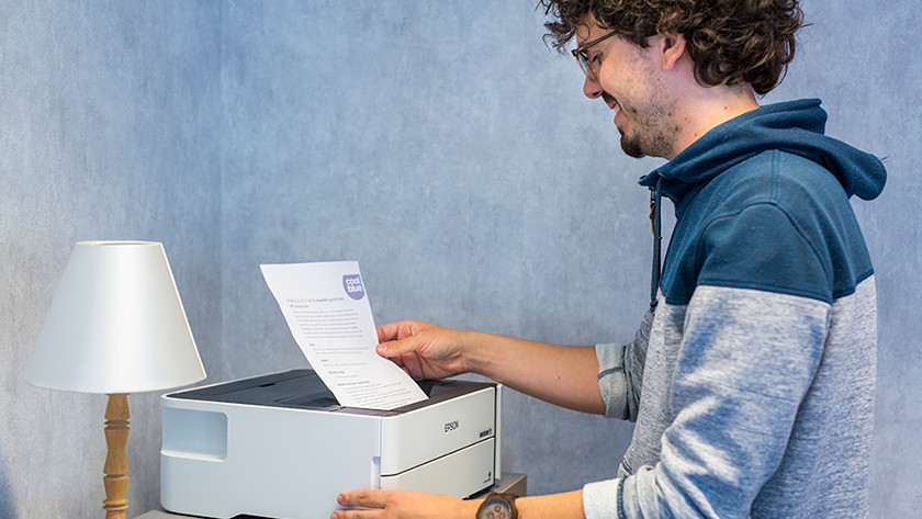 Man haalt Coolblue document uit printer.