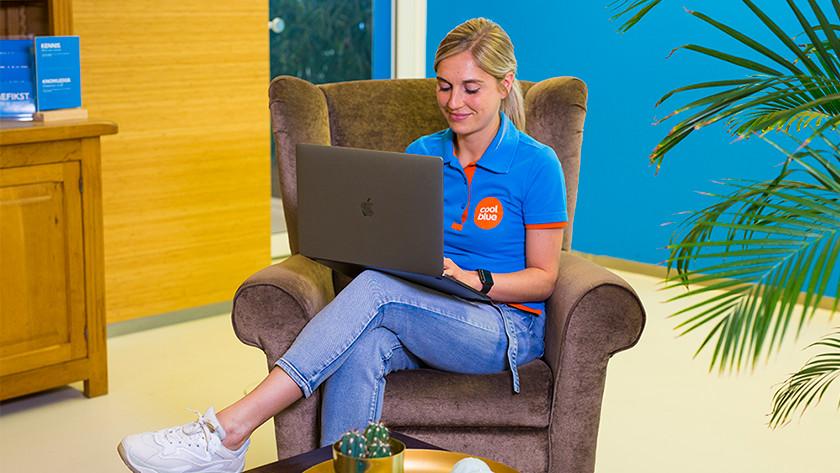 Meisje werkt achter MacBook Pro op loungestoel.