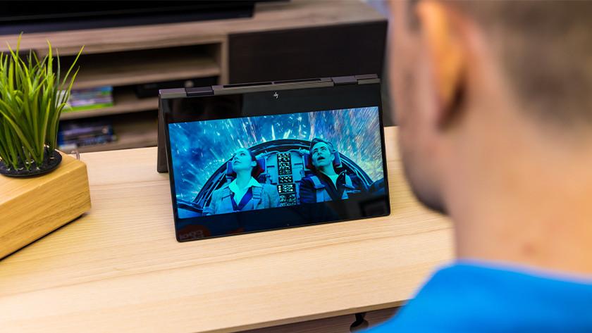 Man kijkt film op laptop in tentstand.