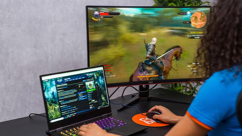Witcher 3 spelen op een gaming laptop en gaming monitor.