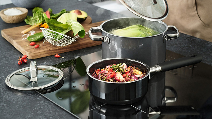 Induction cooktop with pans and vegetables