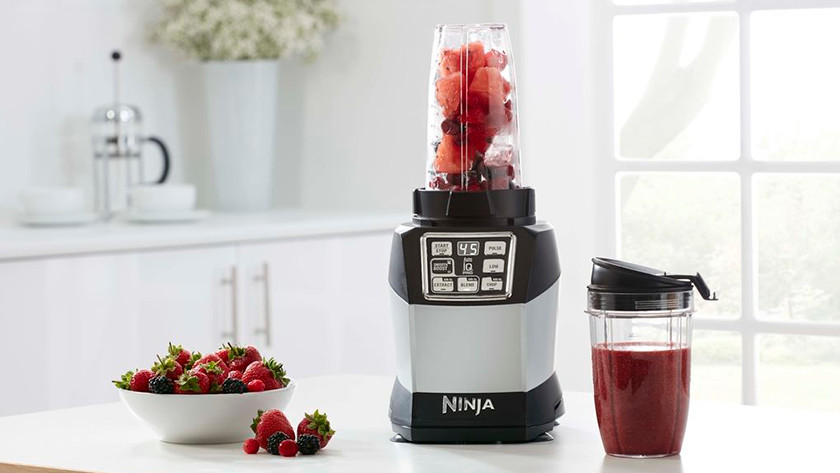 Blender with red fruit and smoothie cup with red smoothie