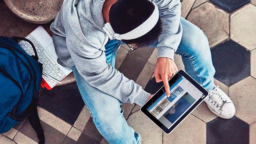 Man met koptelefoon gebruikt touchscreen laptop in tabletmodus.