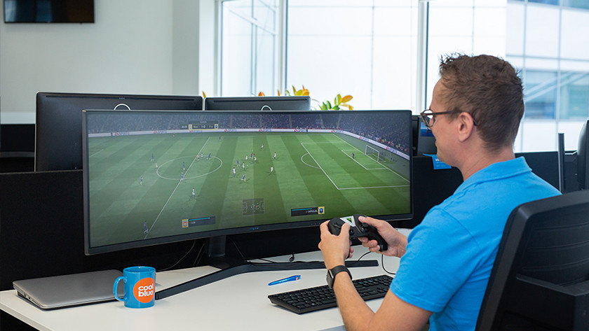 Man playing Fifa on ultrawide monitor for console gaming