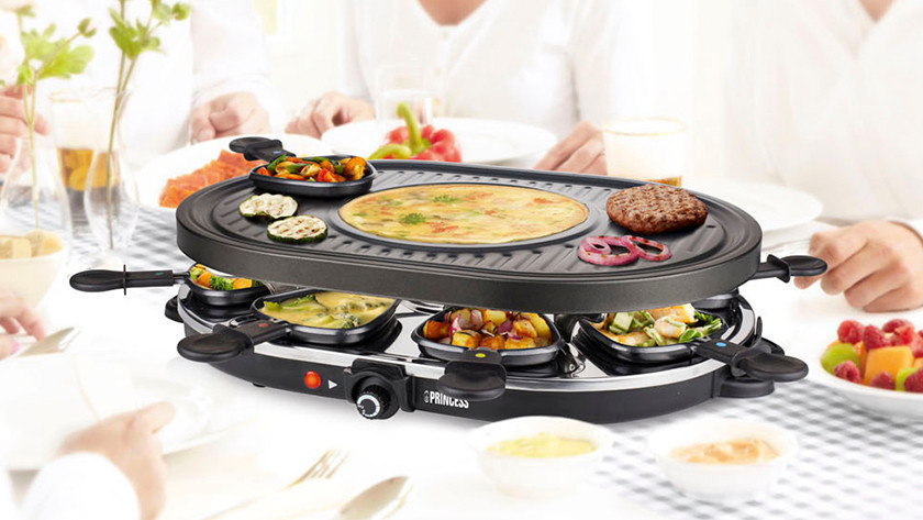 Oval raclette grill with grill and flat griddle